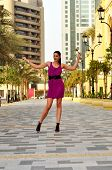 Young Beautiful Woman In Purple Dress Posing On The Street