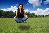 Teen Girl Sits Suspended Above a Grassy Field