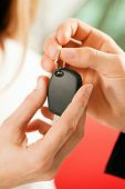Woman buying car - key being given