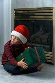 Boy In Santa Hat Shaking Gift
