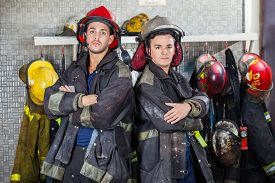 image of firemen  - Portrait of confident young firemen standing arms crossed at fire station - JPG