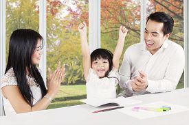 foto of applause  - Image of two young hispanic parents giving applause on their child at home after finishing homework - JPG