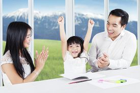 stock photo of applause  - Young parents giving applause on their daughter after finishing school assignment at home - JPG