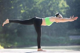 picture of virabhadrasana  - Beautiful sporty fit blond young woman in green sportswear working out outdoors standing in Warrior III posture  - JPG