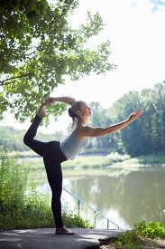 image of shiva  - Beautiful sporty fit blond young woman doing yoga backbend on summer day on the lake Natarajasana Dancing Shiva yoga pose  - JPG
