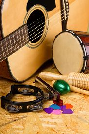 stock photo of bongo  - Vertical photo with several musical instruments on wooden OSB board as acoustic guitar with several colorful picks guiro harmonica bongo and others - JPG
