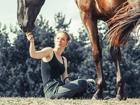 pic of feeding horse  - Young woman girl feeding and taking care of brown horse. Female with animal outdoor. ** Note: Visible grain at 100%, best at smaller sizes - JPG