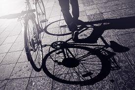 stock photo of monochromatic  - Man Pushing Bicycle Street Shadow on Pavement Urban Setting Retro Toned Monochromatic Image - JPG
