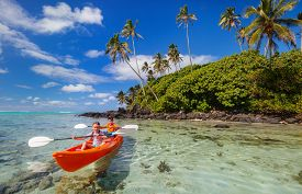 picture of kayak  - Kids enjoying paddling in colorful red kayak at tropical ocean water during summer vacation - JPG