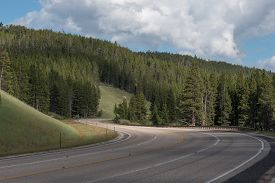 picture of twisty  - Twisty asphalt mountain road cutting through hills and forest in the Bighorn Mountains of Wyoming - JPG