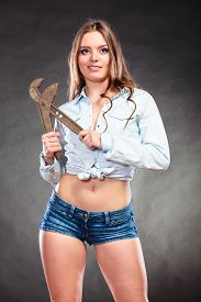 picture of gender  - Sexy alluring seductive woman holding monkey wrench gas grips - JPG