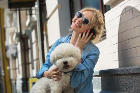 pic of bichon frise dog  - Cute blonde in sunglasses and a bright blue denim shirt emotionally talking on a cell phone - JPG