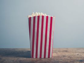 image of matinee  - A box of popcorn on a wooden table - JPG