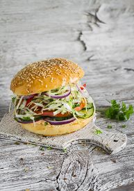 stock photo of veggie burger  - delicious veggie burger with cabbage tomato cucumber onions and peppers on a light wooden surface - JPG
