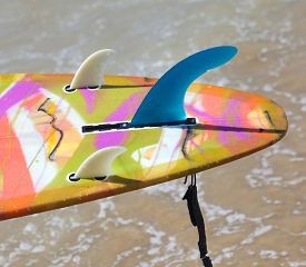 stock photo of fin  - Close up of fins of longboard on the beach - JPG