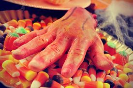 picture of amputation  - closeup of a scary amputated hand on a tray with some different Halloween candies and cobwebs - JPG