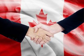 picture of politician  - Two politicians shaking hands in front of canada flag background - JPG