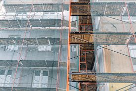 picture of reconstruction  - apartment building exterior under reconstruction with scaffolding and green netting - JPG
