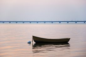 foto of anchor  - An old rowing boat anchored in a calm bay with the swedish Oland bridge in the background