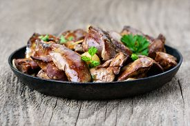 picture of liver fry  - Chicken liver in frying pan on wooden table - JPG