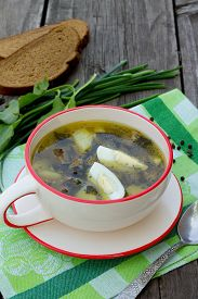 pic of sorrel  - Sorrel soup with egg and greens on a wooden background - JPG