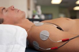 stock photo of stimulating  - Physical therapy or chiropractic treatment of a male patient - JPG