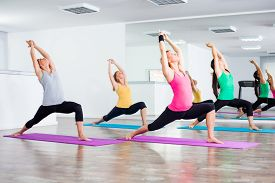 stock photo of virabhadrasana  - Four girls practicing yoga - JPG