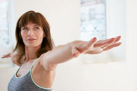 stock photo of virabhadrasana  - Portrait of fitness woman stretching her hands and looking away - JPG