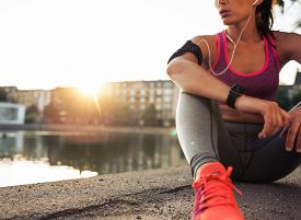 pic of jogger  - Young woman runner resting after workout session on sunny morning - JPG