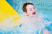 pic of amusement park rides  - Boy splashes down after water slide ride - JPG