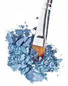 Cepillo de maquillaje con azul gris aplastado sombra de ojos, aislado en blanco Macro