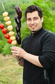 Young Man Holding Skewers With Vegetables, Ready For Bbq