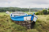 Old Abandoned Wooden Fishing Boat Stranded On Land And Grass. poster