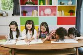 Group Of Little Preschool Kids Drawing Paper With Color Pencils . Portrait Of Children Friends Educa poster