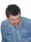 stock photo of male face  - Portrait of the thoughtful man with black hair in a jeans shirt - JPG