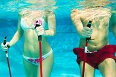 Fitness - a young couple (man and woman) doing sports and gymnastics or water aerobics under water i