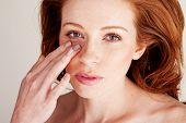 Mulher atraente ruiva no retrato de beleza, misturando a Fundação para o rosto com a ponta dos dedos