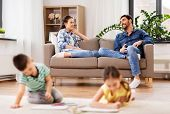 family, leisure and people concept - happy mother and father sitting on sofa and looking at their ch poster