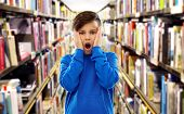 childhood, expressions and people concept - shocked or scared boy touching his face over book shelve poster