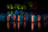 HANGZHOU, CHINA - NOVEMBER 26: A cast performs Zhang Yimou's outdoor folk musical show 'Impressions West Lake' in an outdoor stage built on the lake on November 26, 2011 in West Lake, Hangzhou, China.