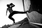 stock photo of parkour  - Monochrome image of a female traceur using momentume and speed to propel herself through the air between two buildings while participating in parkour - JPG