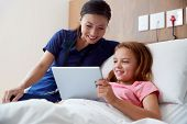 Female Nurse With Girl Lying In Hospital Bed Looking At Digital Tablet Together poster