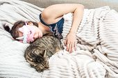 Portrait Of A Young Woman With A Sleep Mask On Her Face And Sleeping Pajamas Hugging Her Cat. Concep poster