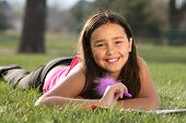 pic of american indian  - Portrait of a cute multiracial girl lying on the grass - JPG