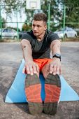 A Male Athlete Doing Gymnastics Stretching Muscles, Training Muscles Flexibility Plasticity On Mat,  poster