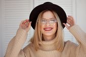 Charming Young Woman In A Soft Sweater And Glasses, In A Black Felt Hat. Portrait Of A Happy Smiling poster