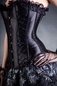 Close-up shot of elegant woman in black corset, studio shot