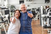 Senior Couple Giving Thumbs Up At Gym. Happy Couple Of Seniors Gesturing Thumbs Up At Fitness Center poster