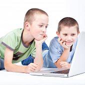 Niño utilizando una computadora portátil moderno mientras se está acostado en el piso (aislado sobre fondo blanco)