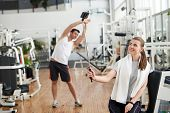 Girl Taking Selfie At Fitness Club. Woman Taking Selfie With Monopod While Man Working Out On The Ba poster